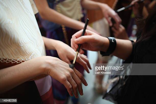 A model prepares backstage at the Royal College of Art's graduate fashion show on May 31 2012 in London England Twenty eight postgraduate students of...