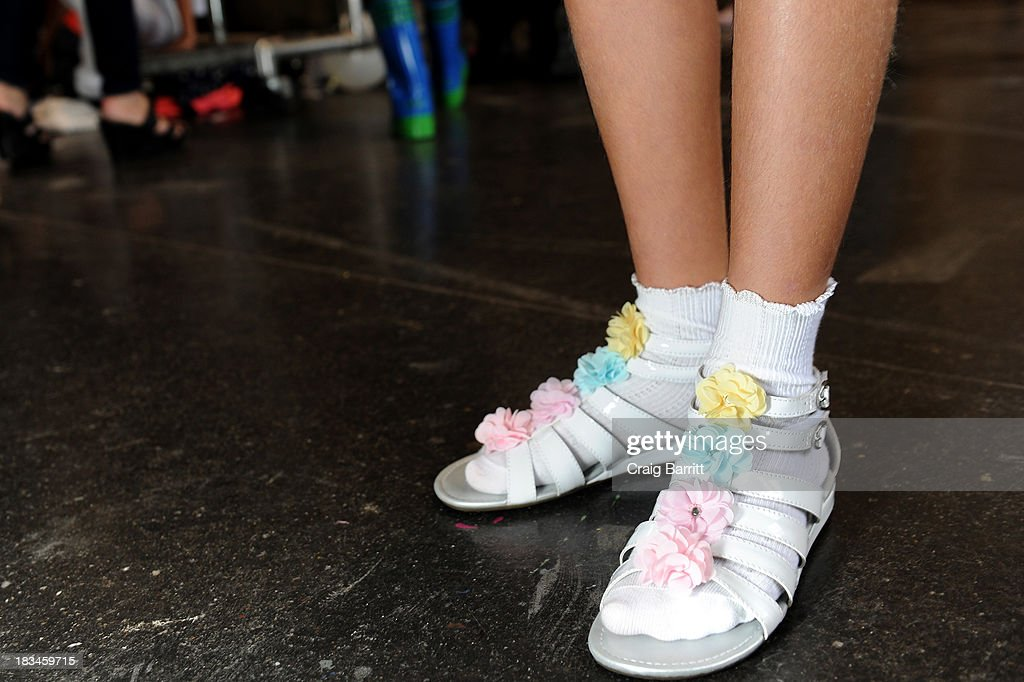 A model prepares backstage at the Stride Rite Children's Group Fashion Showcase at petitePARADE on October 6, 2013 at Industria Superstudios in New York City.