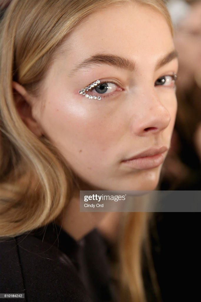 A model prepares backstage at the Tome Fall 2016 fashion show during New York Fashion Week: The Shows at The Dock, Skylight at Moynihan Station on February 14, 2016 in New York City.