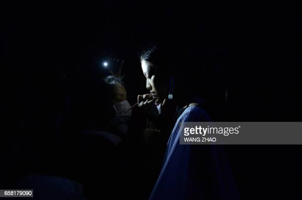 TOPSHOT A model prepares backstage before a creation designed by Young Designers from BIFTMMUSCU at China Fashion Week in Beijing on March 27 2017 /...