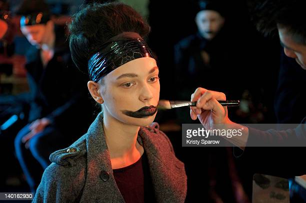 A model prepares backstage before the Devastee ReadyToWear Fall/Winter 2012/13 show as part of Paris Fashion Week at Alexandre III Port des Champs...