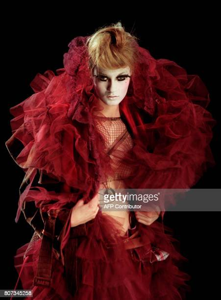 A model presents a burgundy crocodile silk taffeta and silk tulle coat with burgundy hand painted corduroy pants by British designer John Galliano 17...