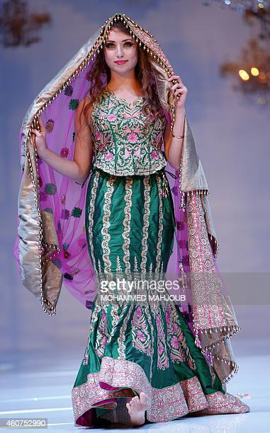 A model presents a creation by Bahraini fashion designer Kobrai alQoseer during the Gulf's Forum of Elegance event on December 21 2014 in the Omani...