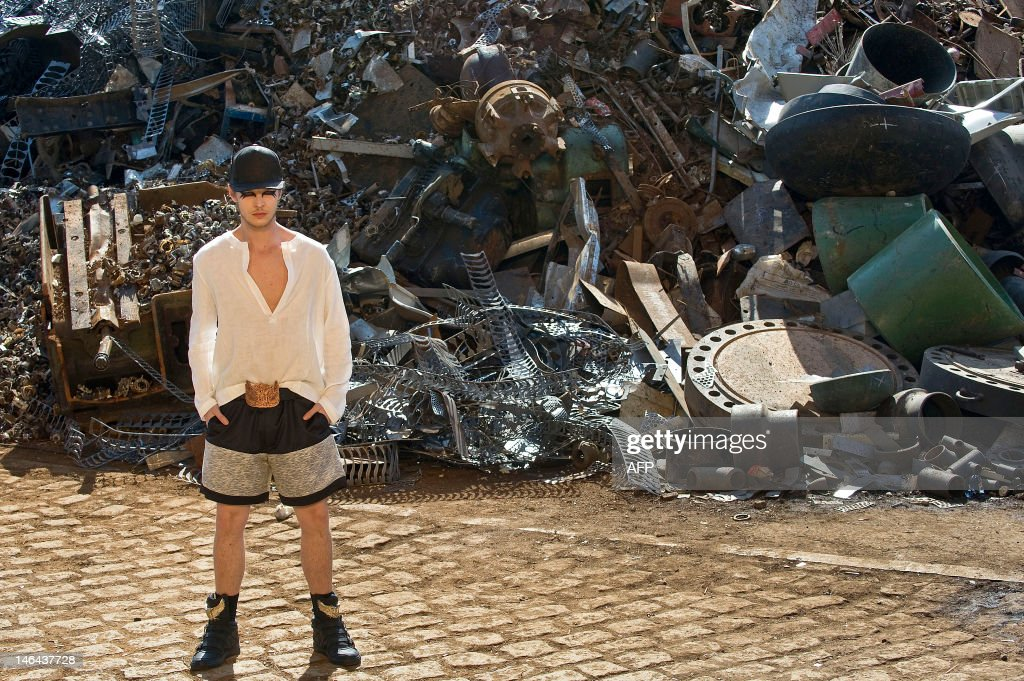 A model presents a creation by Cavalera 2013 summer collection at a junkyard during Sao Paulo Fashion Week in Sao Paulo, Brazil, on June 16, 2012. AFP PHOTO / Nelson ALMEIDA