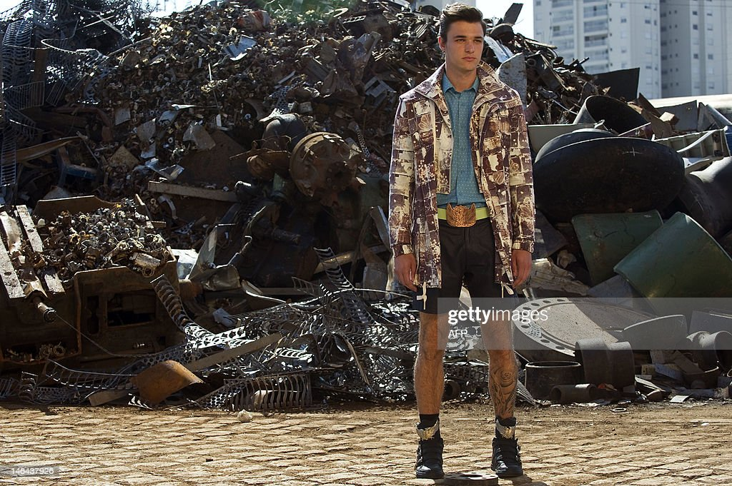A model presents a creation by Cavalera 2013 summer collection at a junkyard during the Sao Paulo Fashion Week in Sao Paulo, Brazil, on June 16, 2012. AFP PHOTO / Nelson ALMEIDA