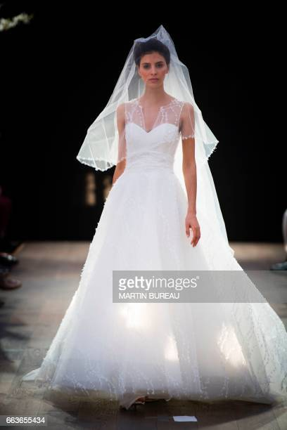 A model presents a creation by Cymbeline Wedding Dresses house on April 1 2017 in Paris / AFP PHOTO / MARTIN BUREAU