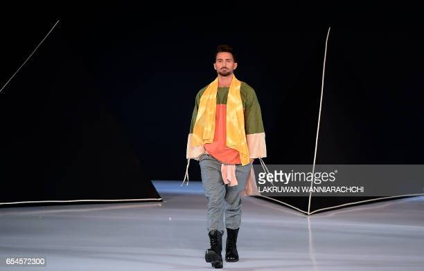 A model presents a creation by fashion designer Catherine Rawson at the Colombo fashion week in Colombo on March 17 2017 / AFP PHOTO / LAKRUWAN...