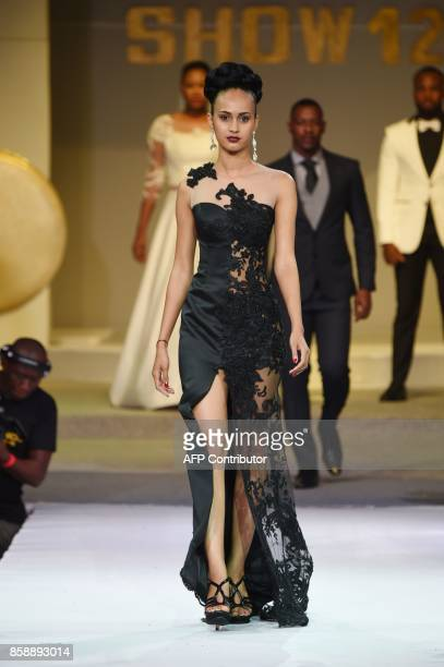 A model presents a creation by Ivorian designer Reda Fawaz during the Africa Fashion show on October 7 2017 in Abidjan / AFP PHOTO / SIA KAMBOU