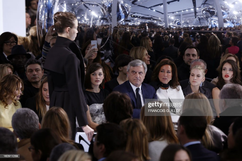 A model presents a creation for Christian Dior next to French actress Marion Cotillard (3L), CEO of Christian Dior Couture Sidney Toledano (C) and wife Katia, French actress Melanie Laurent (2R) and Chelsea Anna Tallarico, daughter of US singer Steven Tyler (R) during the Fall/Winter 2013-2014 ready-to-wear collection show, on March 1, 2013 in Paris.