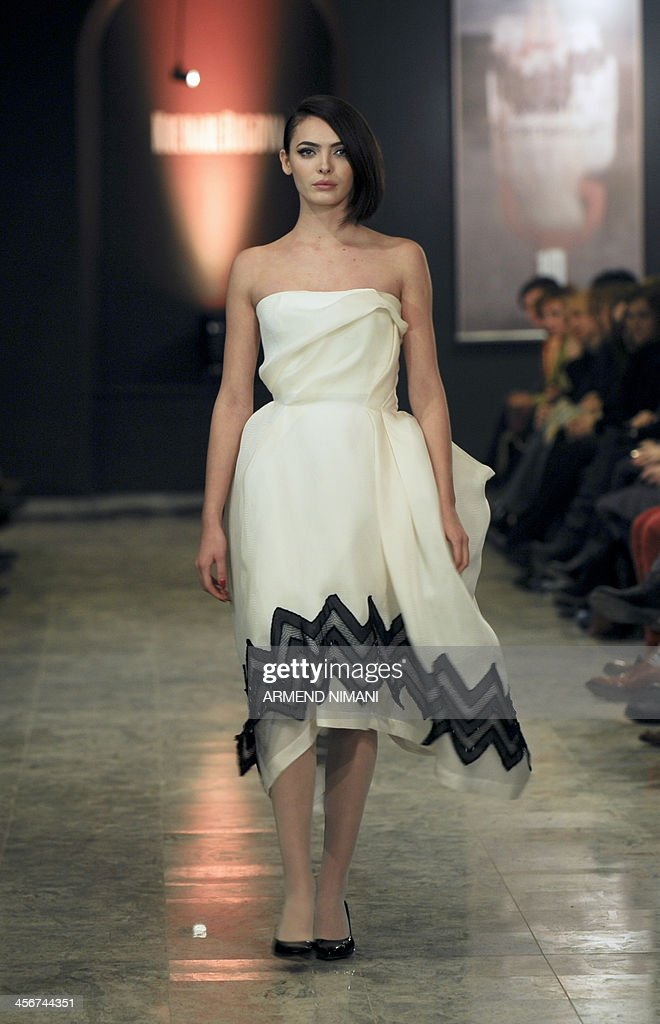 A model presents a creation of the spring/summer collection 'Cinematique' by Kosovar designer Krenare Rugova during a fashion show in Pristina on December 14, 2013.