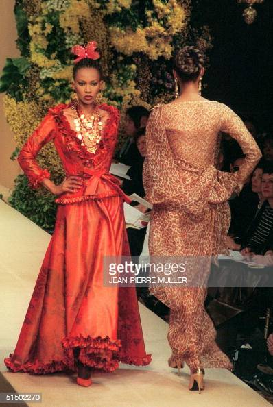 A model presents a gypsy red printed dress as another wearing a gauze dress with panther print leaves the catwalk 19 January 2000 in Paris during...