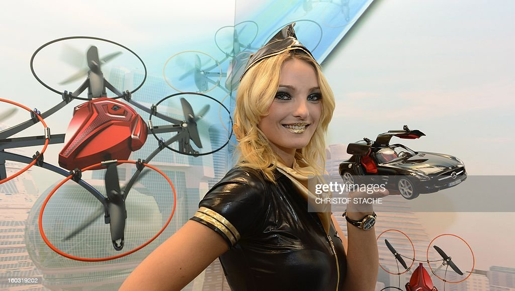 A model presents a remote-controlled car at a booth during the press preview of the international toy fair in Nuremberg, southern Germany, on January 29, 2013. Around 2.700 exhibitors show more than 1 million products at the international toy fair which opens its doors from January 29 to February 4, 2013.