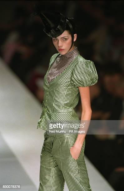 A model presents an Antonio Berardi creation consisting of a black and white checkered trouser suit and black hat during the first day of London...