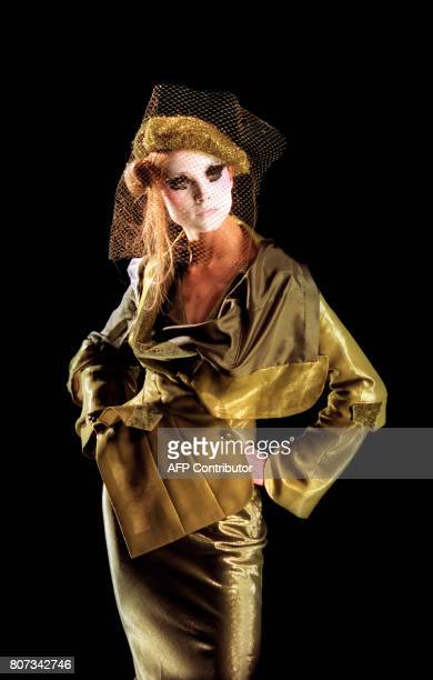 A model presents an olive organza linen and gold lame jacket with an olive lame bias skirt by John Galliano 17 January 2000 for the Christian Dior...