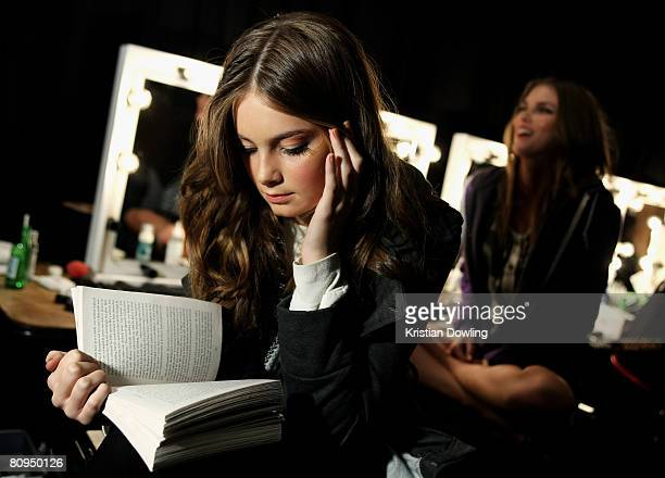 A model reads a book as she prepares backstage prior to the Illionaire show on the fourth day of Rosemount Australian Fashion Week Spring/Summer...