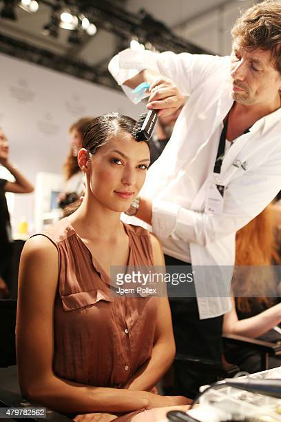 Model Rebecca Mir gets her hair done by Andre Maertens backstage ahead of the Riani show during the MercedesBenz Fashion Week Berlin Spring/Summer...