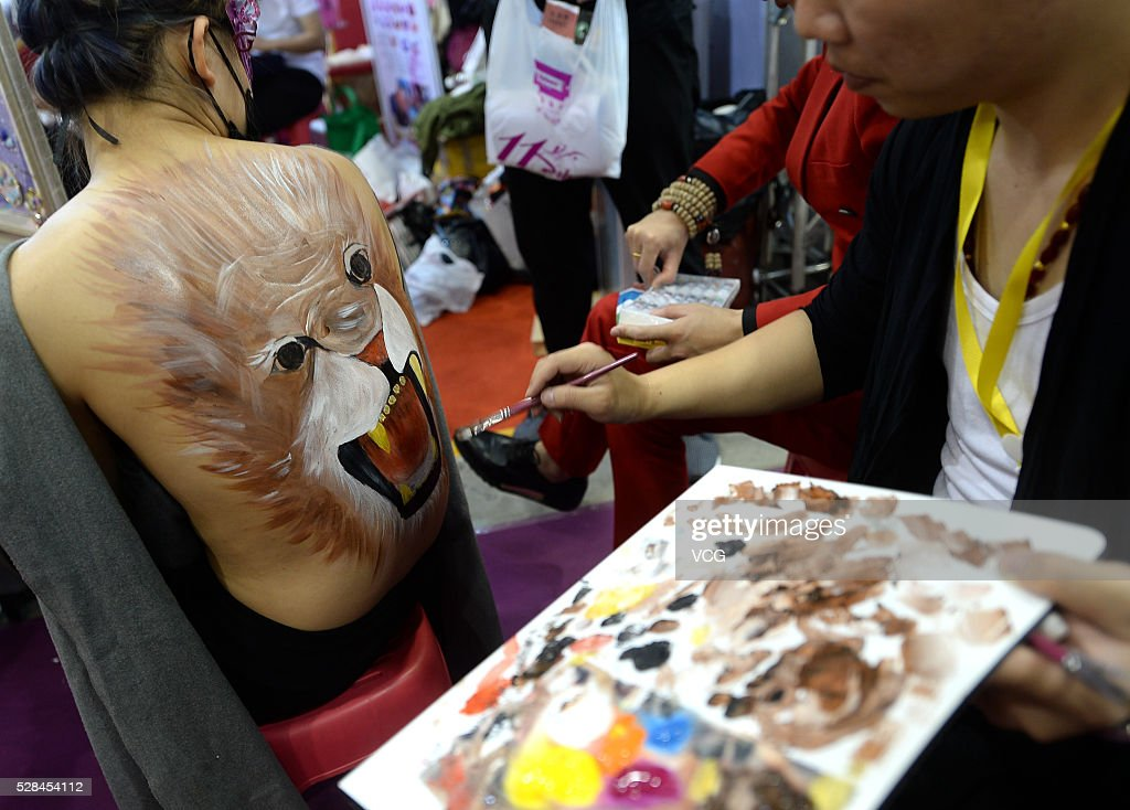A model receives painting on her back during the 31th China (Jinan) International Beauty, Hairdressing & Cosmetics Expo on May 5, 2016 in Jinan, Shandong Province of China. Participants showed various makeups and attire on the exposition.
