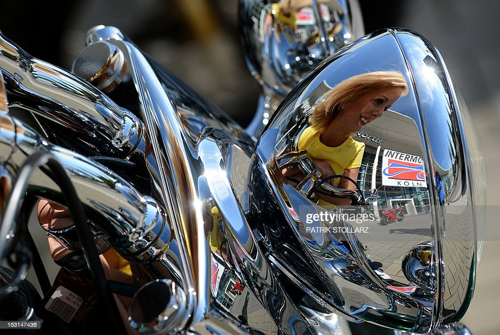 CORRECTION - A model reflects in the chrome plated headlight of a motorcycle during a photocall to promote the intermot fair on October 1, 2012 at the fair grounds in Cologne, western Germany. The intermot international motorcycle, scooter and bicycle fair with around 1,000 exhibitors from 37 companies will run from October 3 to 7, 2012. AFP PHOTO / PATRIK STOLLARZ