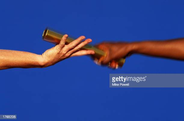 Athletics relay runners exchanging baton closeup