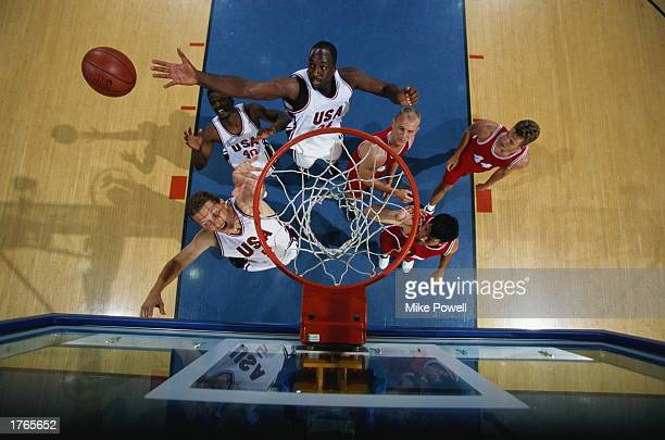 Basketball players gather beneath net one making shot overhead view