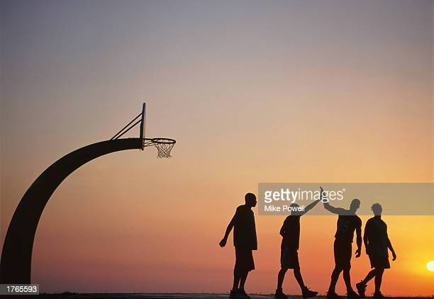 Basketball players on court two doing ''high five'' silhouette