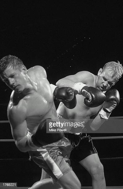 Boxing man delivering punch opponent reeling
