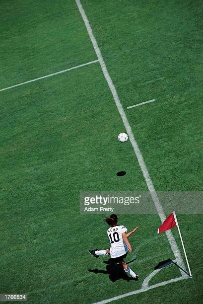 Female soccer player kicking ball aerial view