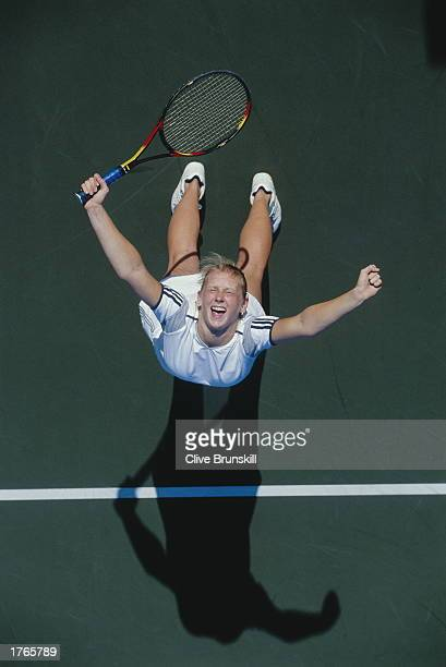 Female tennis player raising arms in celebratory pose overhead view