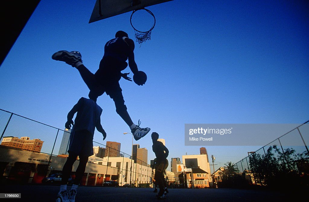 Four men playing street basketball low angle view