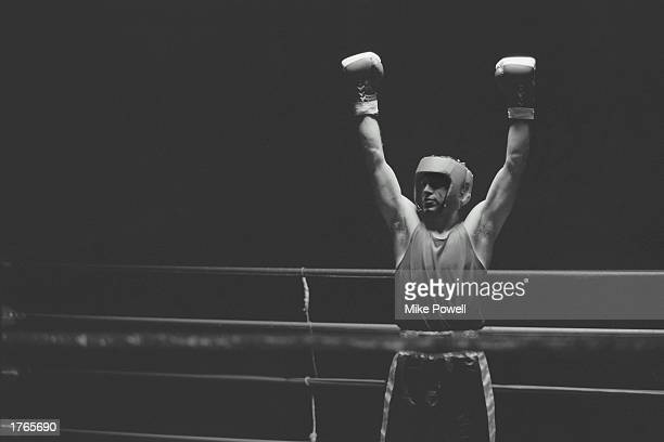 Male boxer standing in ring with arms raised