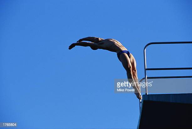 Male diver jumping off diving board low angle view