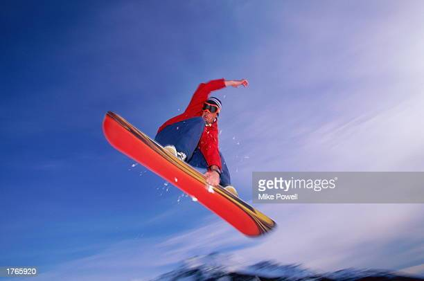 Male snowboarder in midair low angle view