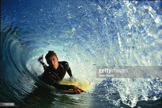 Male surfer lying on surfboard inside tube wave closeup