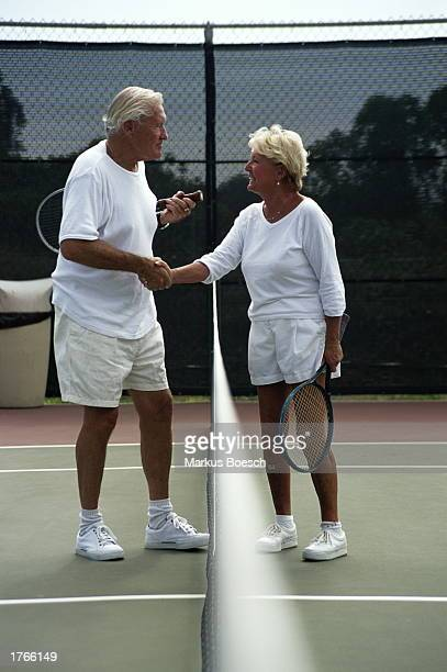 Mature couple shaking hands over tennis net