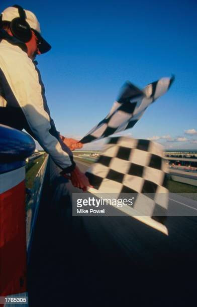Motor racing officials beside track holding chequered flags