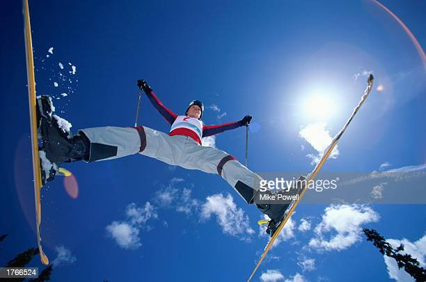 Skier in midair jump legs spread low angle view