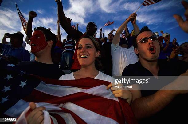 Soccer fans cheering in stands woman holding American flag