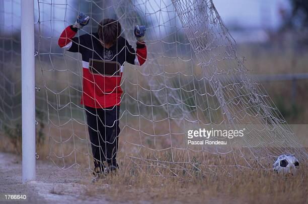Soccer goalkeeper holding netting ball in goal area