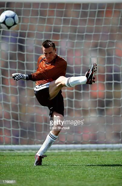 Soccer player kicking ball goal net in background