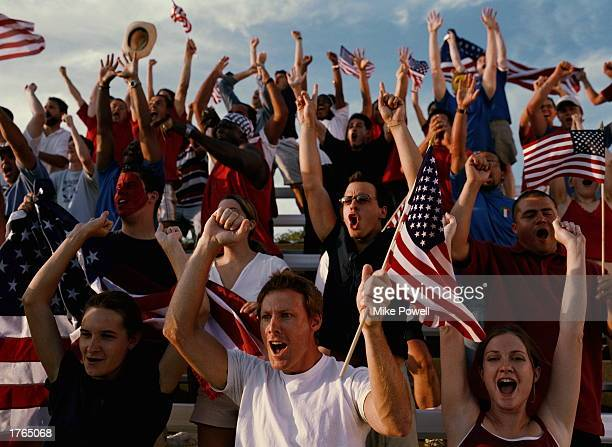 Sports fans cheering from stands carrying USA flags