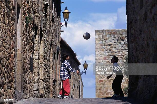 Two boys playing with soccer ball in alley
