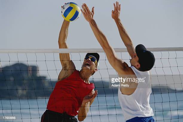 Volleyball two male players jumping for ball at net closeup
