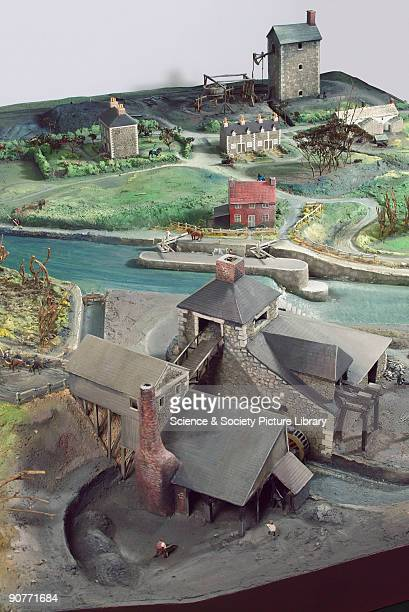 Model representing an 18thcentury British landscape in the foreground is a charcoal burning factory or possibly an ironworks A boat is going through...