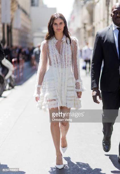 Model Sara Sampaio wearing a white sheer ruffled dress white Chanel bag outside Elie Saab during Paris Fashion Week Haute Couture Fall/Winter...