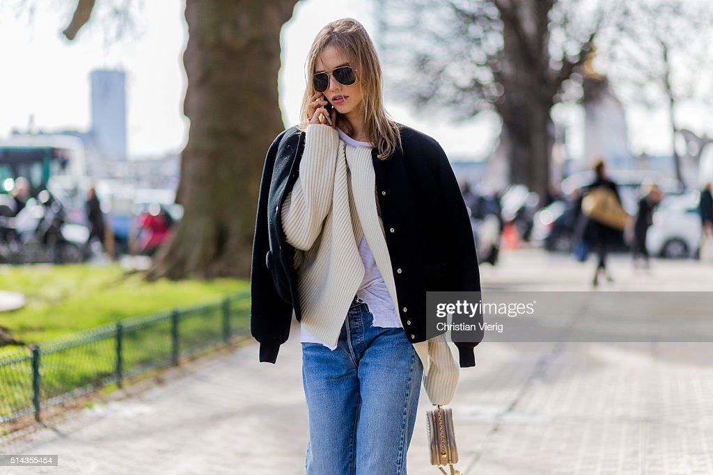 Model Sasha Luss is wearing a black bomber jacket creme sweater blue denim jeans Mini Chanel bag outside Chanel during the Paris Fashion Week...