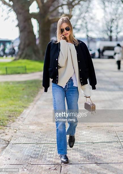 Model Sasha Luss is wearing a black bomber jacket creme sweater blue denim jeans Mini Chanel bag outside Chanel during the Paris Fashion Week...