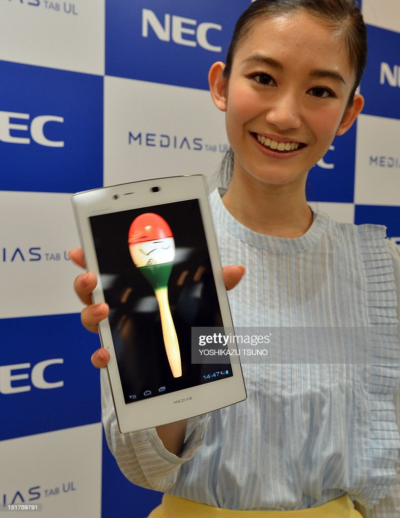 A model 'shakes' maracas as she displays the new tablet device from Japanese electronics manufacturer NEC called 'Medias Tab N-08D' at a preview in Tokyo on September 11, 2012. The new tablet, equipped with a seven-inch touch-screen display, weighs only 249g and will go on sale on September 20 through Japan's mobile communication company NTT DoCoMo. AFP PHOTO / Yoshikazu TSUNO