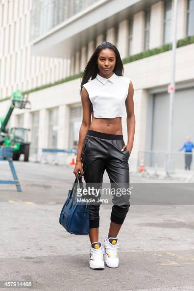Model Sharam Diniz exits the Herve Leger by Max Azria show at Lincoln Center in a top by ASOS pants by BCBG shoes by Reebok and bag by Celine on Day...