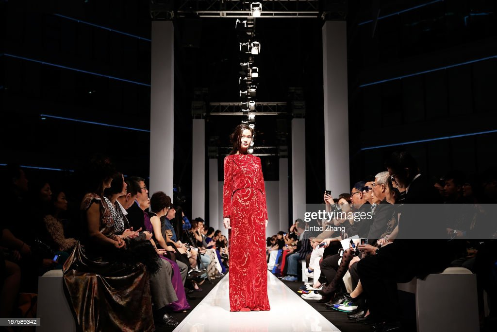 A model showcase designs on the catwalk during the Tadashi Shoji Beijing Store Grand Opening at Beijing Parkview Green on April 26, 2013 in Beijing, China.