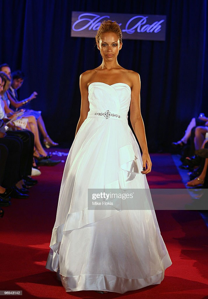 a model showcases affordable wedding dress designs by henry roth on the catwalk at